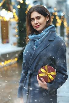 Aantrekkelijke brunette vrouw met geschenkdoos in de buurt van de kerstmarkt tijdens de sneeuwval