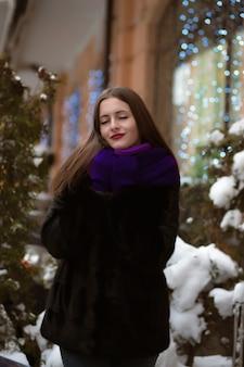 Aantrekkelijke brunette vrouw met gesloten ogen, het dragen van bontjas, poseren op de achtergrond van bokeh