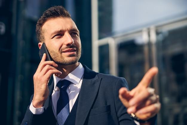 Aantrekkelijke brunette zakenman die tijd buitenshuis doorbrengt terwijl hij op smartphone spreekt en met de vinger wijst