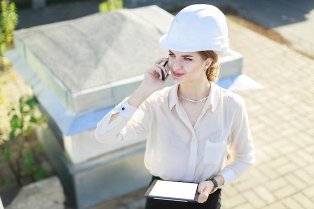 Aantrekkelijke businesslady in witte blouse, horloge, helm en zwarte rok staan op het dak, houden tablet en praten een telefoon
