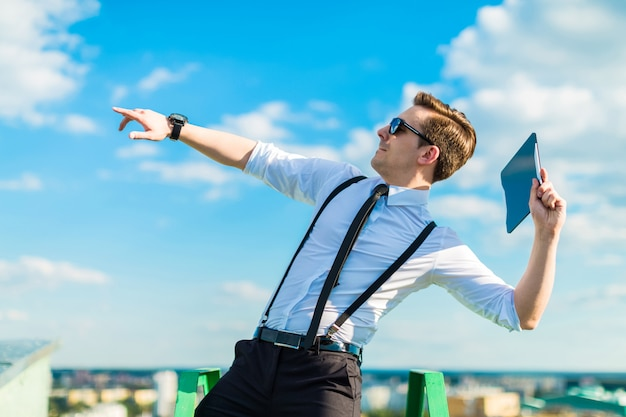 Aantrekkelijke busunessman in wit overhemd, stropdas, bretels en zonnebril gooien tablet vanaf het dak
