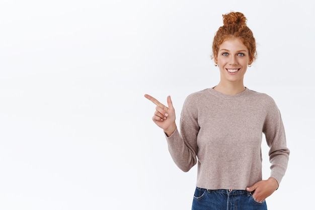 Aantrekkelijke, charismatische roodharige vrouw met krullend haar gekamd in rommelige knot, hand in zak houden, naar links wijzend, product introduceren, tevreden glimlachen als reclame weggeefactie, staande witte muur