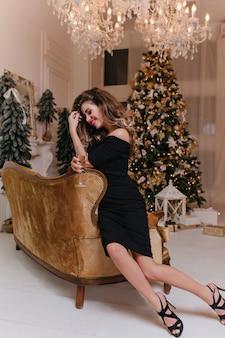 Aantrekkelijke, charmante jonge brunette met krullen glimlacht verlegen en vormt in een luxe appartement met kerstversiering. foto van gemiddelde lengte van gelukkige vrouw met glas champagne
