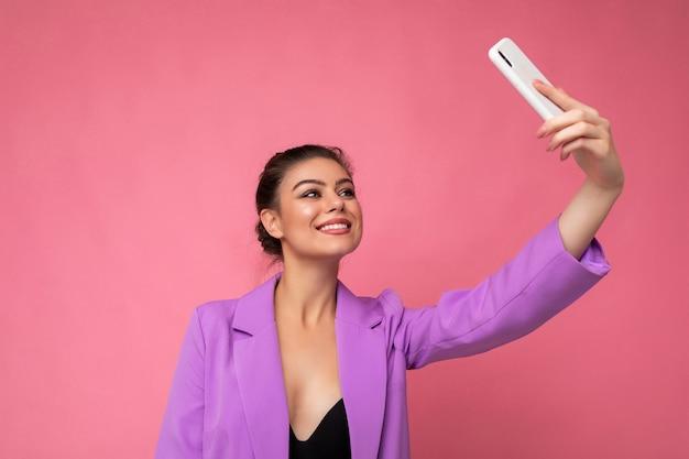 Aantrekkelijke charmante jonge gelukkige vrouw die mobiele telefoon vasthoudt en gebruikt