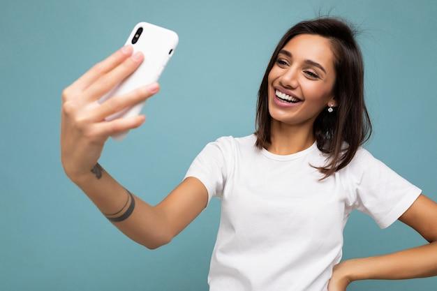 Aantrekkelijke charmante jonge glimlachende gelukkige vrouw die een mobiele telefoon vasthoudt en gebruikt die selfie maakt met stijlvolle kleding