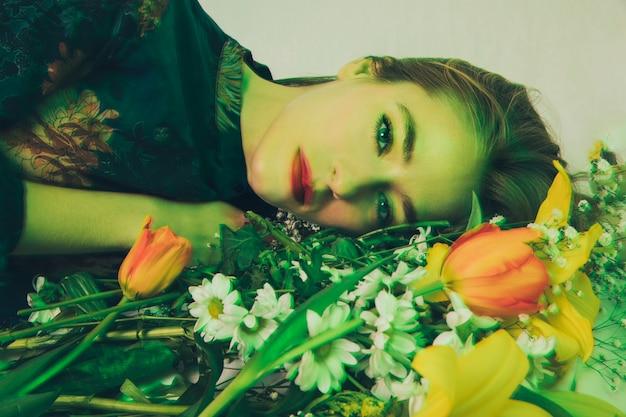 Aantrekkelijke charmante vrouw die met boeket van bloemen in groenheid ligt