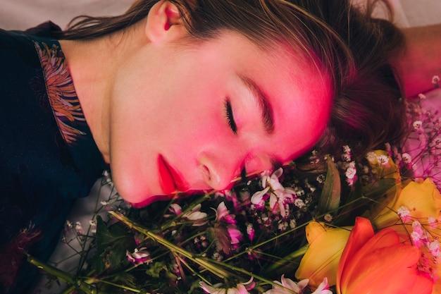 Aantrekkelijke charmante vrouw die met boeket van bloemen in roze ligt