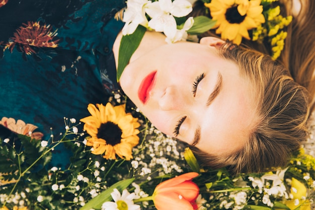 Aantrekkelijke charmante vrouw die tussen bloemen ligt
