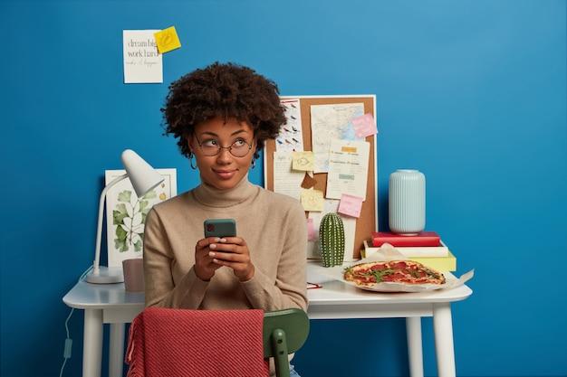 Aantrekkelijke curly haired vrouw werkt op afstand thuis, mobiele telefoon in handen houdt, sms-berichten verzendt, optische bril draagt, poses in eigen gezellige kamer over werkplek.