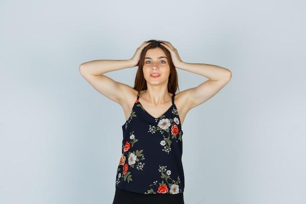 Aantrekkelijke dame die de handen op het hoofd in blouse houdt en verbaasd kijkt, vooraanzicht.