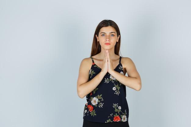 Aantrekkelijke dame die de handen samendrukt in een biddend gebaar in een blouse en er dankbaar uitziet, vooraanzicht.