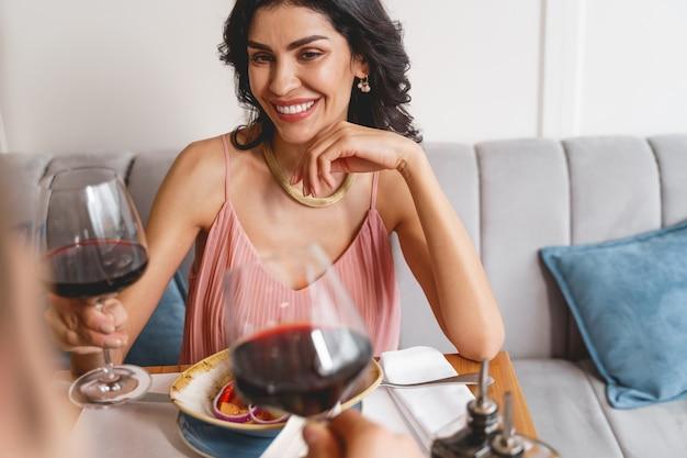 Aantrekkelijke dame die een glas alcoholische drank vasthoudt en een heer met een glimlach aankijkt terwijl ze aan tafel zit met heerlijk eten