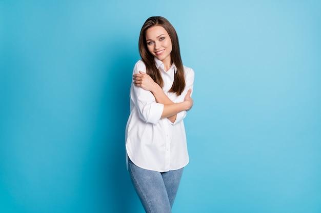 Aantrekkelijke dame goed humeur charmant uiterlijk knuffelen zichzelf dragen wit overhemd jeans geïsoleerde blauwe kleur achtergrond
