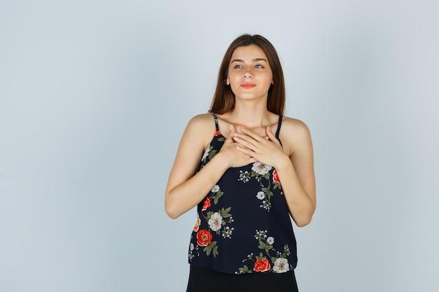 Aantrekkelijke dame hand in hand op de borst in blouse en ziet er tevreden uit, vooraanzicht.