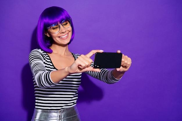Aantrekkelijke dame houdt telefoon nemen selfies spreken skype vrienden dragen specificaties gestreepte pullover geïsoleerde paarse achtergrond