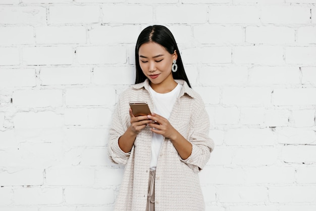 Aantrekkelijke dame in beige vest en t-shirt chats in telefoon op witte bakstenen muur muur