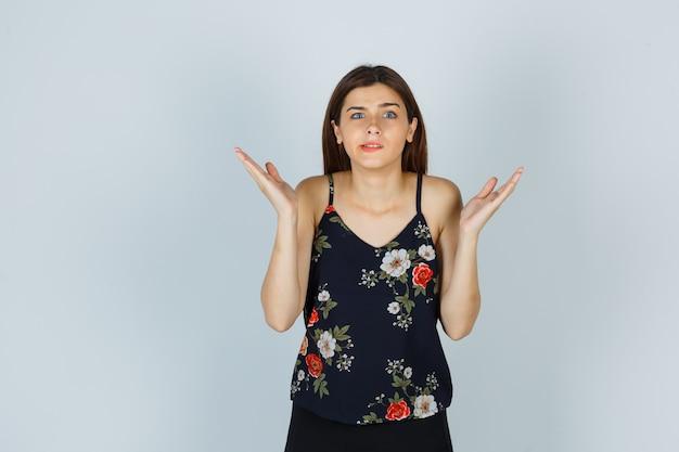 Aantrekkelijke dame in blouse die hulpeloos gebaar toont en verward kijkt, vooraanzicht.