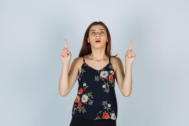 Aantrekkelijke dame in blouse die omhoog wijst en verrast kijkt, vooraanzicht.