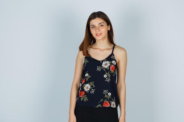 Aantrekkelijke dame in blouse poseren terwijl ze staan en er optimistisch uitzien, vooraanzicht.