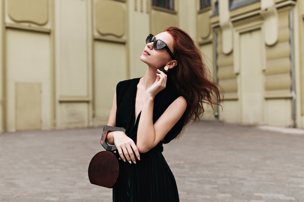 Aantrekkelijke dame in fluwelen jurk en zonnebril vormt buiten