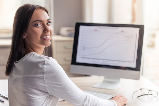 Aantrekkelijke dame in stijlvolle kleding gebruikt een computer.