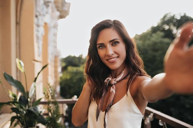 Aantrekkelijke dame in zijden witte top neemt selfie op balkon. de vrij donkerbruine vrouw in beige sjaal maakt foto in zonneschijn.