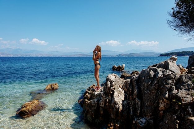 Aantrekkelijke dame in zwarte bikini die zich op rotsen dichtbij overzees bevindt