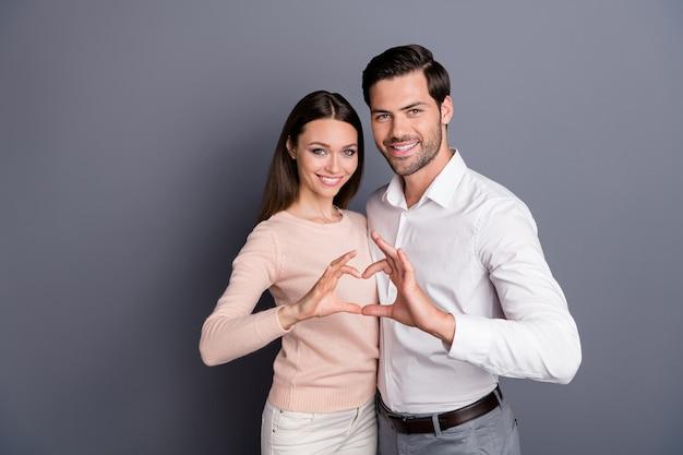 Aantrekkelijke dame knappe kerel paar staan dicht knuffelen maken hart figuur