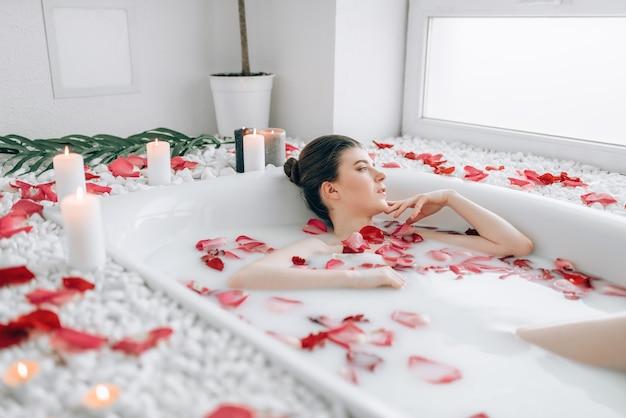 Aantrekkelijke dame liggend in bad met rozenblaadjes