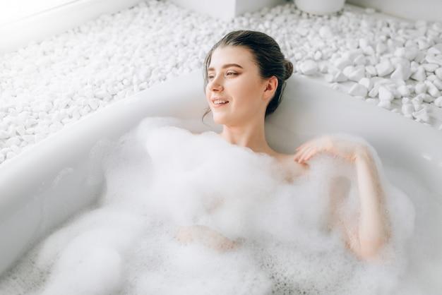 Aantrekkelijke dame liggend in bad met schuim, bovenaanzicht