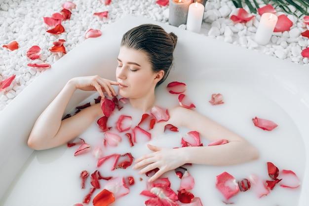 Aantrekkelijke dame liggend in het bad met schuim en versierd met rozenblaadjes.