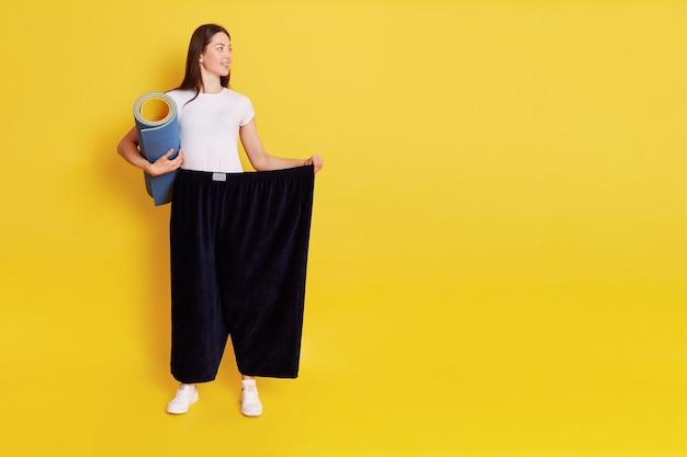 Aantrekkelijke dame met perfect lichaam die keremat vasthoudt, een te grote broek draagt, wegkijkt naar kopie ruimte voor reclame, helpt broek met hand vast te houden, geïsoleerd over gele muur.
