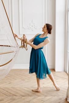 Aantrekkelijke danseres in blauwe jurk in lichte studio