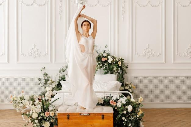 Aantrekkelijke danseres in een elegante jurk op een bed met bloemen