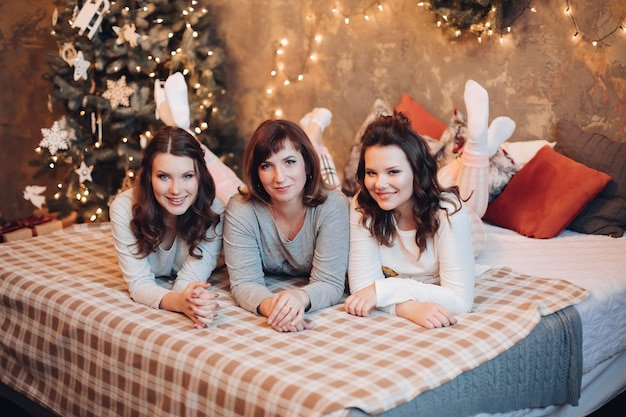 Aantrekkelijke donkerbruine dames - moeder en haar twee tienerdochters in pyjama die op bed liggen die voorzijde bekijken