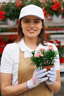 Aantrekkelijke donkerbruine vrouw die leuke bloempot houdt