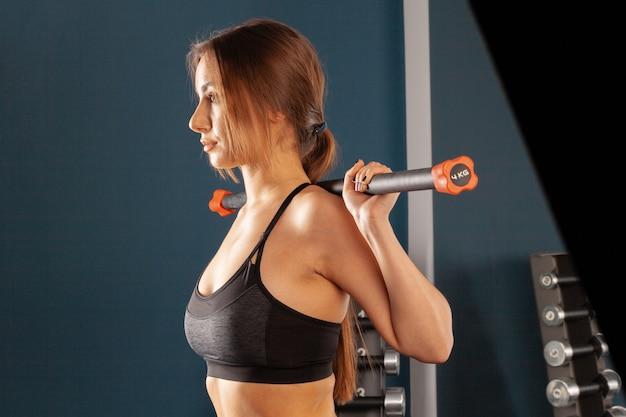 Aantrekkelijke donkerbruine vrouw die met bodybar in een gymnastiek uitwerkt