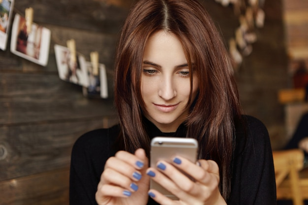 Aantrekkelijke donkerbruine vrouw die tekstbericht op generische smartphone typen terwijl het wachten op vriend, die bij koffie zitten. leuke europese vrouw bekijkt foto's via sociale media