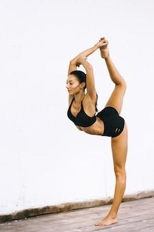 Aantrekkelijke donkerbruine vrouw die yogaoefeningen in bikini op een witte oppervlakte doet