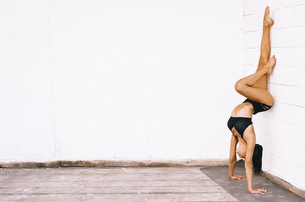 Aantrekkelijke donkerbruine vrouw die yogaoefeningen in seksuele bikini op een witte achtergrond doet
