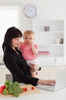 Aantrekkelijke donkerbruine vrouw in kostuum die haar baby in haar wapens houden terwijl het werken met haar laptop