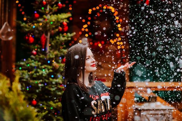 Aantrekkelijke donkerbruine vrouw in zwarte kerstmissweater en het rode lippen stellen