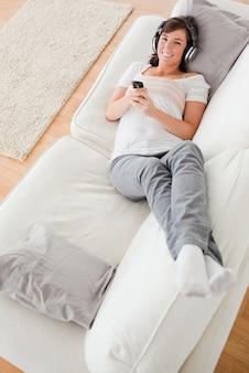 Aantrekkelijke donkerbruine vrouw op de telefoon terwijl het liggen op een bank