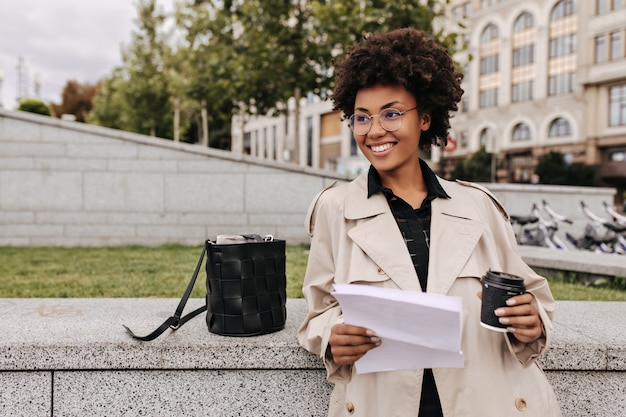 Aantrekkelijke donkere vrouw in beige trenchcoat en bril glimlacht, houdt koffiekopje en vel papier buiten vast