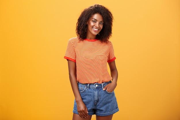 Aantrekkelijke donkere vrouw met krullend haar met hand in zak van denim shorts glimlachend vreugdevol poseren over oranje muur