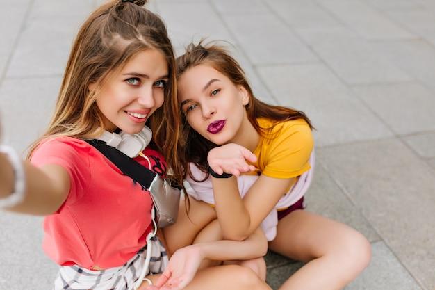 Aantrekkelijke donkerharige meisje zittend op de grond en lucht kus verzenden terwijl haar blonde zus foto van zichzelf neemt