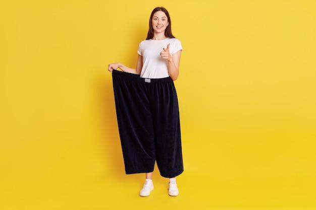 Aantrekkelijke donkerharige vrouw die oude grote broek draagt na gewichtsverlies, heeft een gelukkige, trotse uitdrukking, wijst wijsvinger naar de camera, motiveert om dun te worden, geïsoleerd over gele muur.