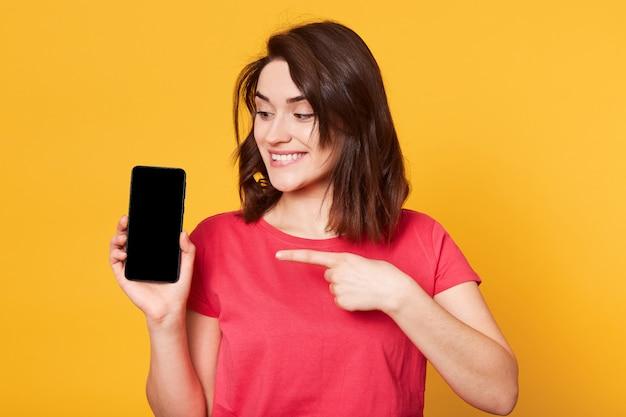 Aantrekkelijke donkerharige vrouw glimlachend en wijzend op leeg scherm van mobiele, adverteert nieuwe gadget, kijkt naar telefoon, casual outfit dragen, poseren geïsoleerd over geel