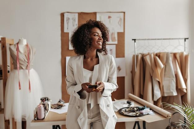 Aantrekkelijke donkerhuidige krullende brunette vrouw in oversized jas en witte broek glimlacht, houdt telefoon vast en leunt op tafel in kantoor van modeontwerper