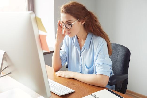 Aantrekkelijke doordachte roodharige zakenvrouw kijken naar het scherm met geconcentreerde uitdrukking